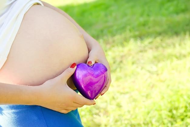 Stuk speelgoed hart dichtbij met buik van zwangere vrouw