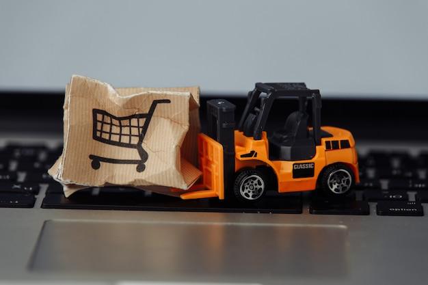 Stuk speelgoed heftruck met doos op laptop close-up