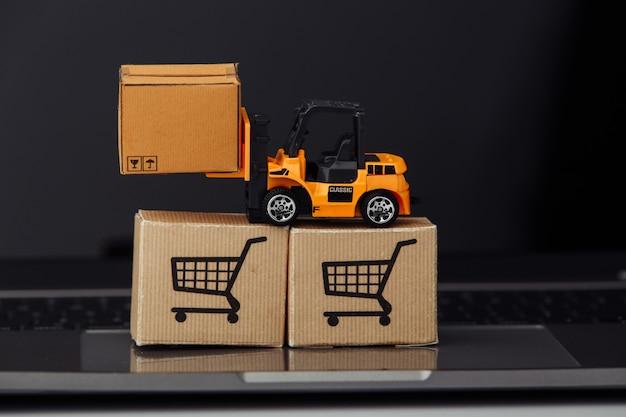 Stuk speelgoed heftruck met dozen op laptop