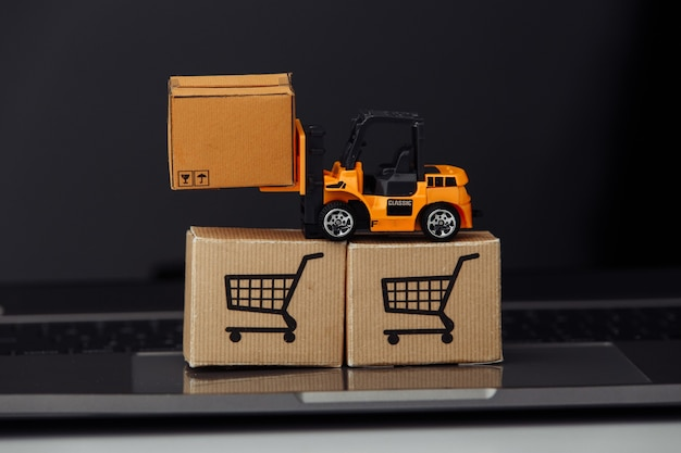 Stuk speelgoed heftruck met kartondozen op laptop. logistiek en groothandelsconcept.
