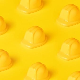 Stuk speelgoed helmpatroon over gele achtergrond, beschermingshoed voor bouw