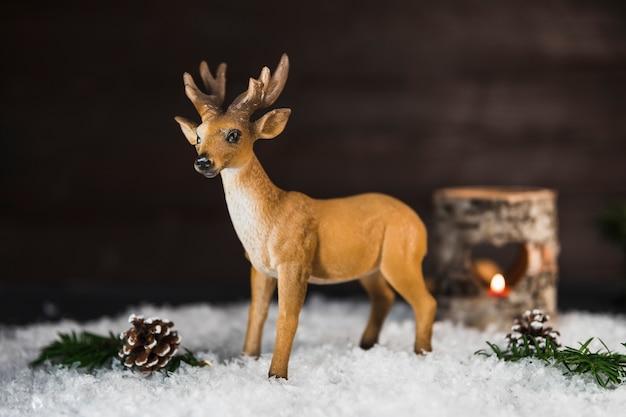 Stuk speelgoed herten dichtbij winkelhaken en takjes op sneeuw