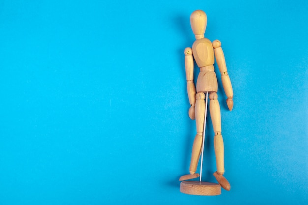 Stuk speelgoed houten pop op gekleurde blauwe achtergrond