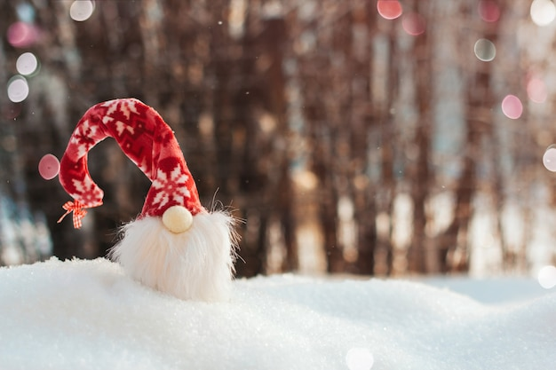 Stuk speelgoed kabouter in een rode hoed in de sneeuw. kerst kopie ruimte