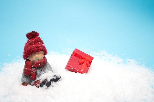 Stuk speelgoed kerstmiself zit in de sneeuw, copyspace