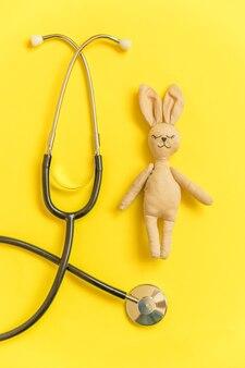 Stuk speelgoed konijntje en de stethoscoop van het geneeskundemateriaal op gele achtergrond wordt geïsoleerd