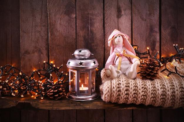 Stuk speelgoed konijntje met wollen sjaalslinger en lantaarn op houten achtergrond