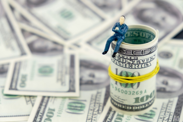 Stuk speelgoed mensen modelzitting op een bundel van geld op een zwarte achtergrond.