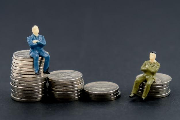 Stuk speelgoed model van mensenzitting op een stapel muntstukken op een zwarte achtergrond.