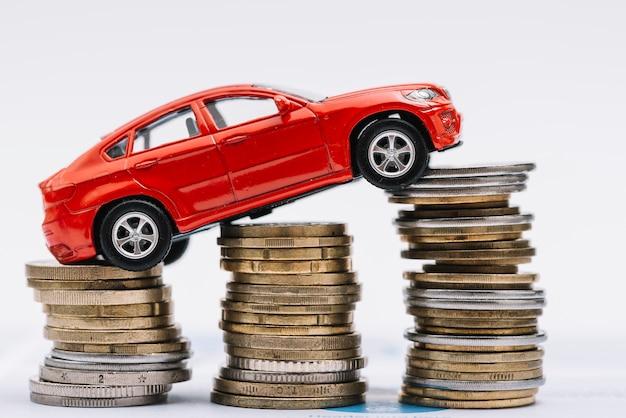 Stuk speelgoed rode auto over de stapel toenemende muntstukken tegen witte achtergrond