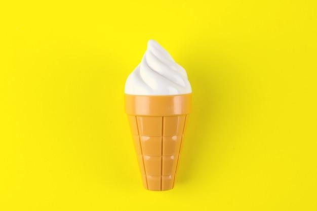 Stuk speelgoed roomijs op gele achtergrond. concept van schadelijk kunstmatig voedsel. fast food.