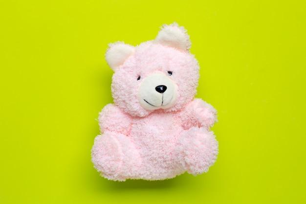 Stuk speelgoed roze beer op groene achtergrond.