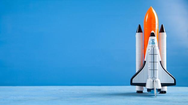 Stuk speelgoed space shuttle op blauwe achtergrond. raket lancering
