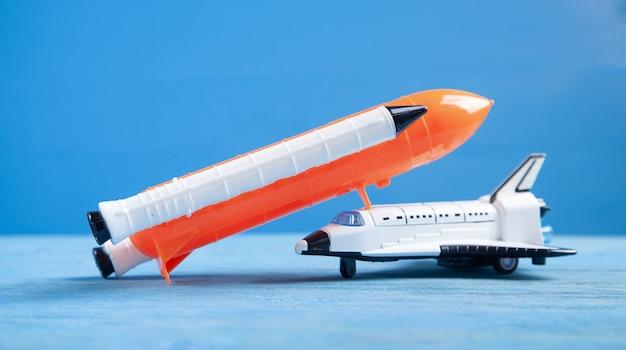 Stuk speelgoed space shuttle op blauwe muur. raket lancering