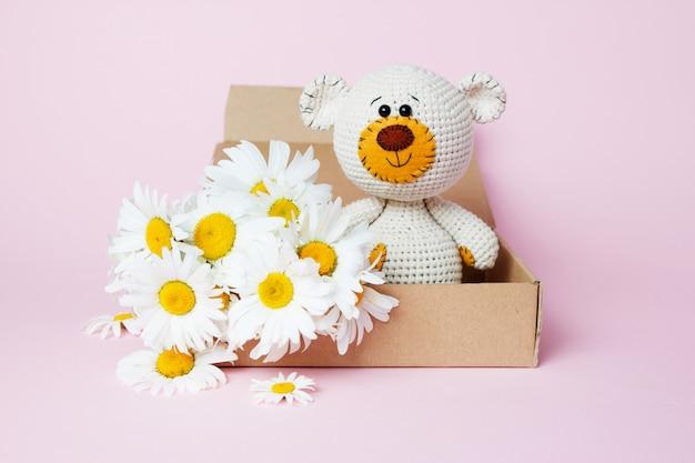 Stuk speelgoed teddybeer in een ambachtdoos met madeliefjes op een roze achtergrond worden geïsoleerd die. baby achtergrond. ruimte kopiëren, bovenaanzicht