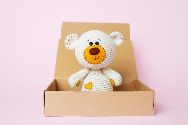 Stuk speelgoed teddybeer in een ambachtdoos op een roze achtergrond wordt geïsoleerd die. baby achtergrond. ruimte kopiëren, bovenaanzicht