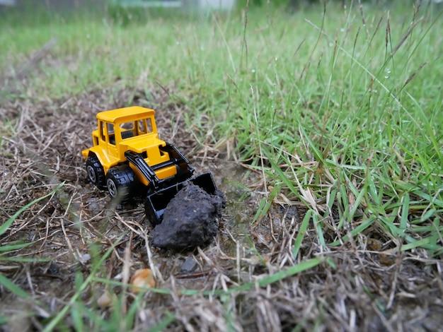 Stuk speelgoed tractor op grond. model van de tractor op de grond. trekker op de grond