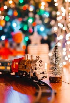 Stuk speelgoed uitstekende stoomlocomotief op de vloer onder een verfraaide kerstboom op a van de slinger van bokehlichten.
