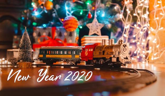 Stuk speelgoed uitstekende stoomlocomotief op de vloer onder een verfraaide kerstboom op een achtergrond van de slinger van bokehlichten.