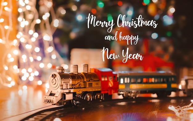Stuk speelgoed uitstekende stoomlocomotief op de vloer onder een verfraaide kerstboom op een slinger van bokehlichten.