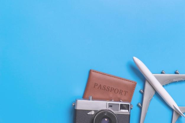 Stuk speelgoed vliegtuig bovenop paspoort met uitstekende camera op blauwe exemplaarruimte