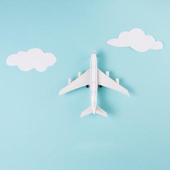 Stuk speelgoed vliegtuig en wolken op blauwe achtergrond
