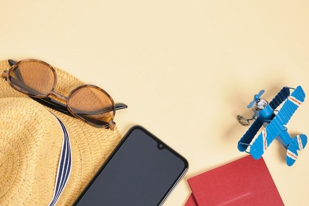 Stuk speelgoed vliegtuig, strohoed, smartphone, zonnebril, wekker en paspoorten op beige achtergrond, reis, veilig strandvakantieconcept
