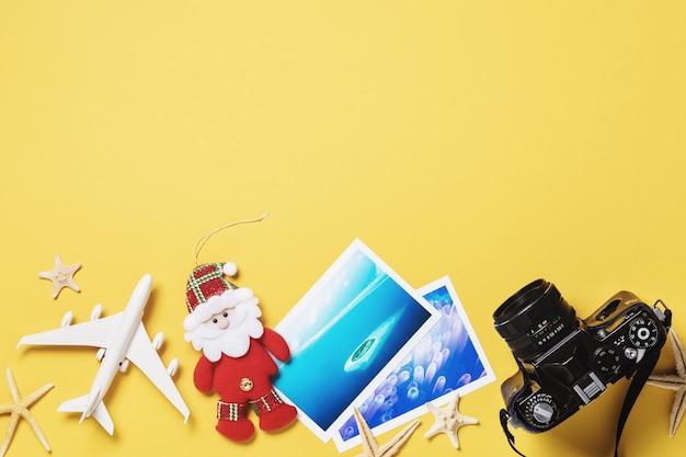 Stuk speelgoed vliegtuigfoto's en camera op een gele achtergrond met het concept van de reisplanning van kerstmis met exemplaarruimte