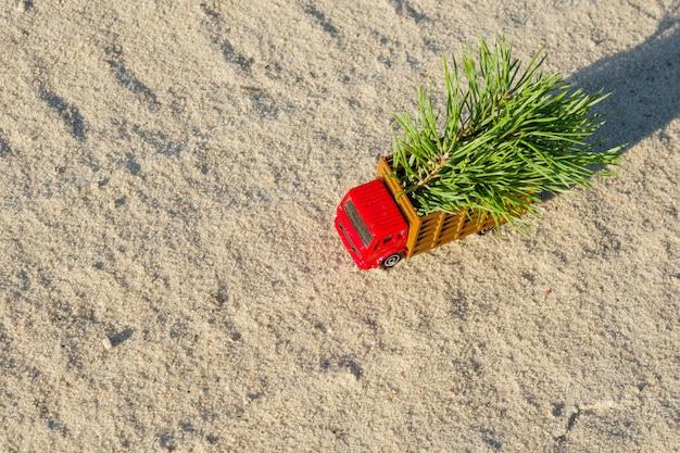 Stuk speelgoed vrachtwagen met kerstboom op de bosweg van het land