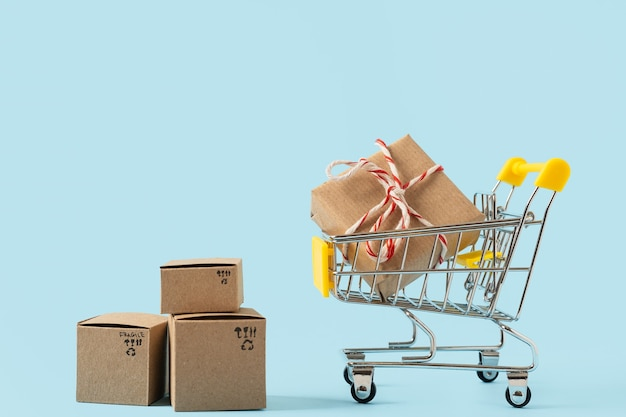 Stuk speelgoed winkelwagentje met dozen op blauwe achtergrond