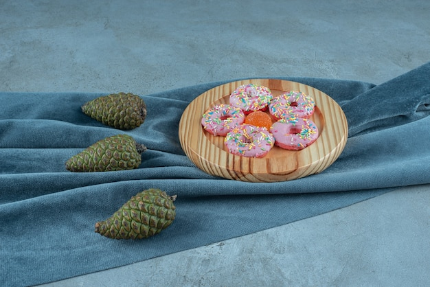 Stuk stof onder dennenappels en een schaal met donuts op textiel.