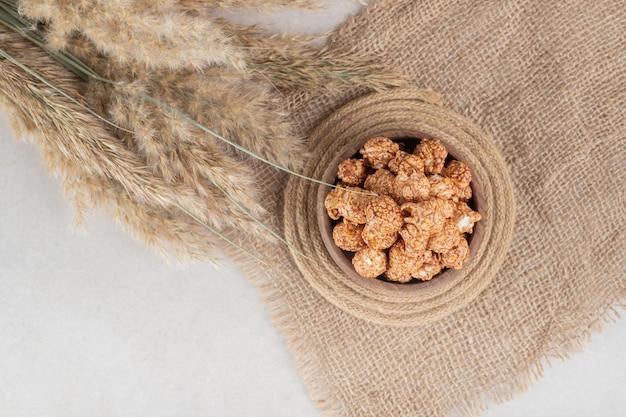 Stuk stof, onderzetter, kom met popcorn met karamelsmaak en stengels van naaldgras op marmeren tafel.