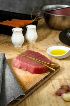 Stuk tonijn vlees op een houten bord met keuken