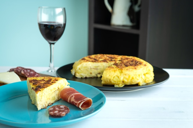 Stuk van aardappelomelet met ham en worst op een blauw bord met een glas wijn op een witte achtergrond. kopieer ruimte.