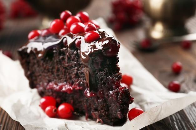 Stuk van chocoladetaart met veenbessen op perkament, close-up