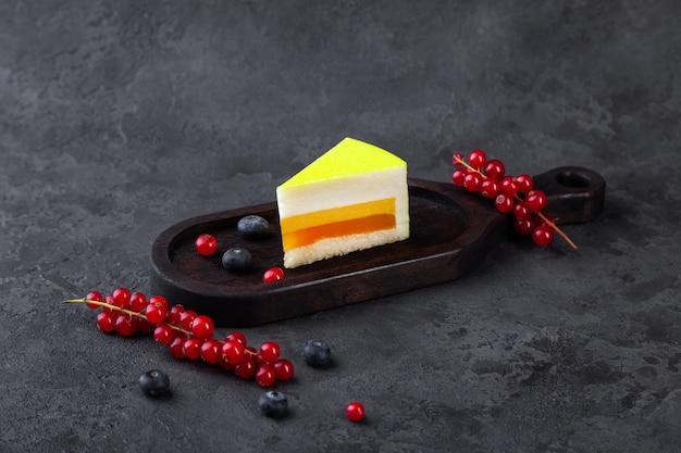 Stuk van de cake van de soufflécitroen op houten plaat, met bosbes en rode aalbes