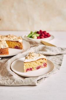Stuk van de heerlijke frambozencake met baiser op een bord