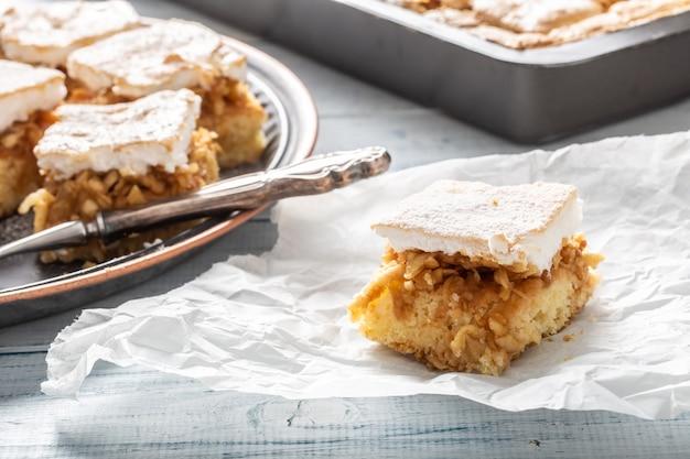 Stuk van een appeltaart met een losgeklopt eiwit op een servet met een bakplaat op de achtergrond.