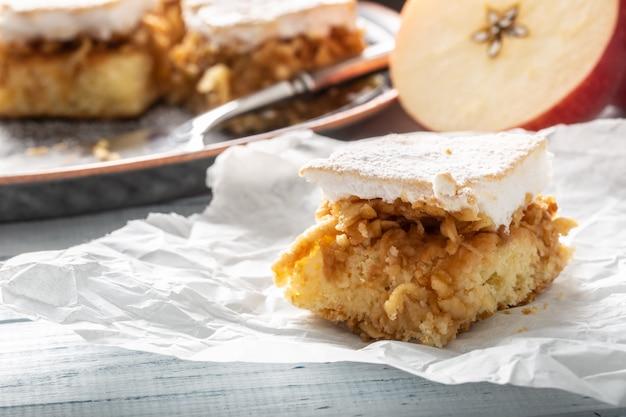 Stuk van een appeltaart met een losgeklopt eiwit op een servet met een vers gesneden appel op de achtergrond.
