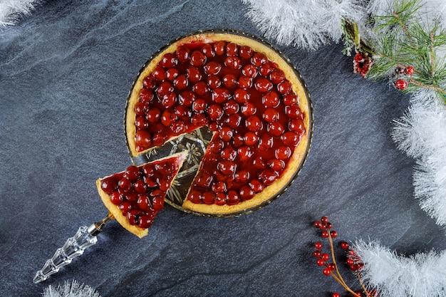 Stuk van kersenkaastaart op cakeschop. kerst inhoud.