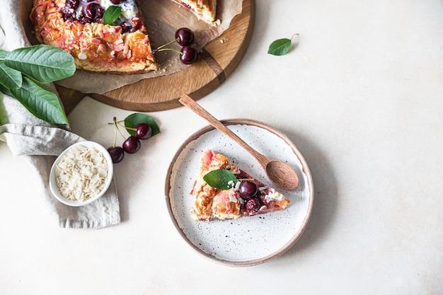 Stuk van open taart of galette met kersen-, amandel- en vanille-ijs, lichte achtergrond. bovenaanzicht.