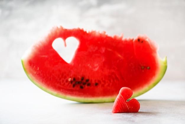 Stuk van watermeloen met hartvorm op grijze concrete achtergrond. valentijnsdag