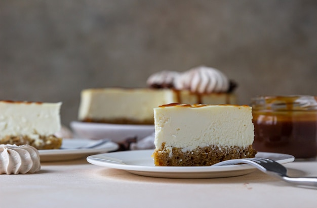 Stuk van wortel vanille cheesecake met gezouten karamel topping en meringue op een witte keramische plaat