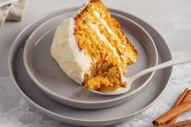 Stuk van wortel zelfgemaakte cake met witte room (roomkaas) op een grijze achtergrond. feestelijk dessertconcept.
