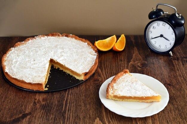Stuk van zelfgemaakte taart met citroen en sinaasappel vulling op een houten tafel