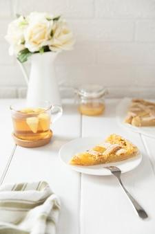 Stuk van zelfgemaakte zandkoek citroentaart bestrooid met poedersuiker op een bord.