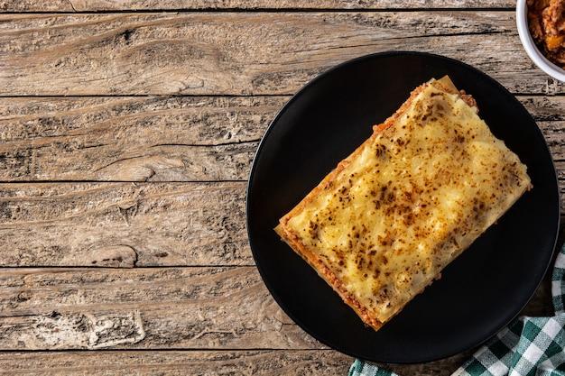 Stuk vlees lasagne op zwarte plaat op rustieke houten tafel