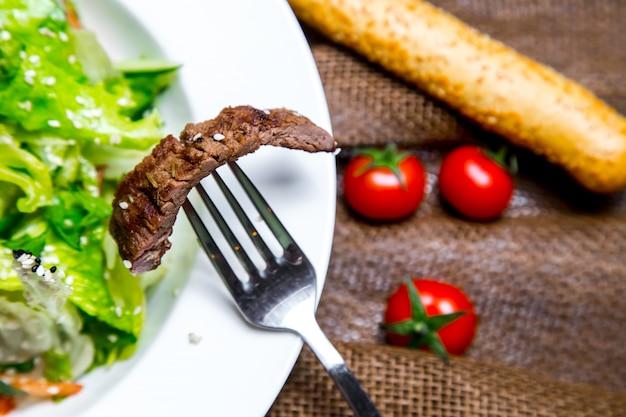 Stuk vlees salade op folk tonato grissini zijaanzicht