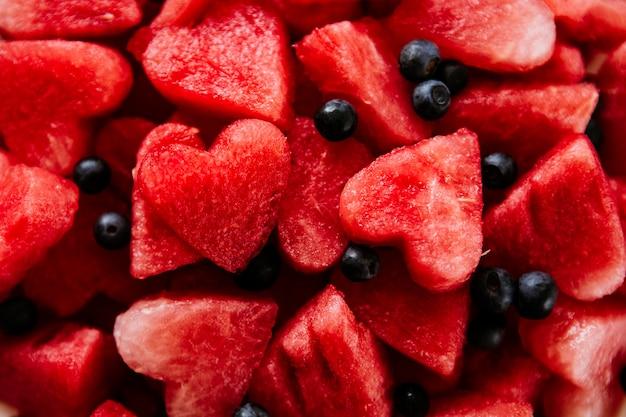 Stuk watermeloen en harten bij witte achtergrond