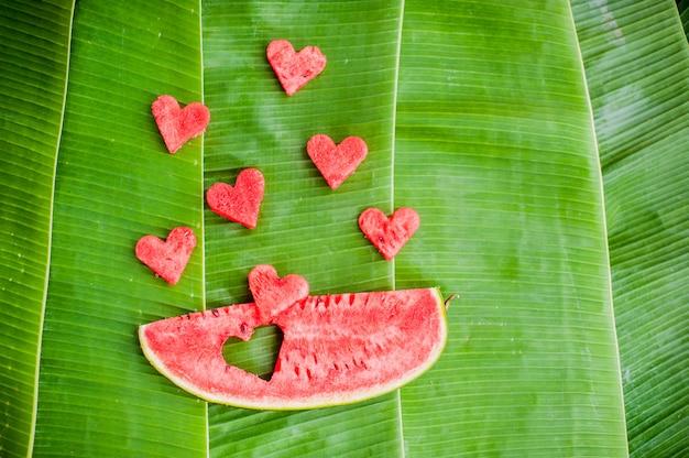 Stuk watermeloen en harten op de achtergrond van bananenbladeren. plat liggen